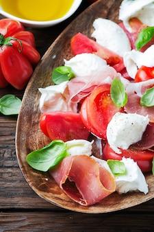 Итальянский салат капрезе с ветчиной, базиликом и моцареллой
