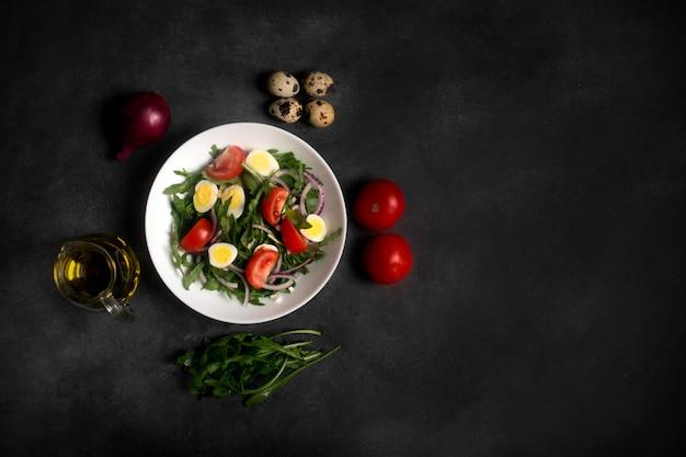 Italian salad prepared with arugula, mozzarella, eggs. black background