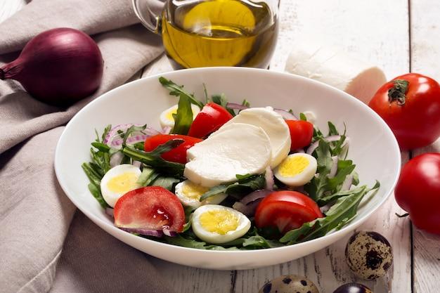 Итальянский салат с рукколой, моцареллой, яйцами. белый деревянный фон