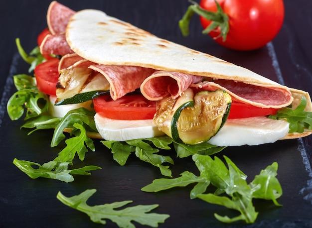 Italian sandwich wraps or piadina with mozzarella, tomato, salami slices, grilled zucchini and arugula on a black slate plate