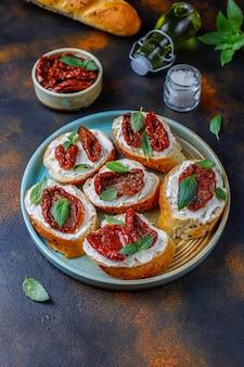 イタリアのサンドイッチ-チーズ、ドライトマト、バジルのブルスケッタ