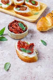 イタリアのサンドイッチ-ブルスケッタとチーズ、ドライトマト、バジル。