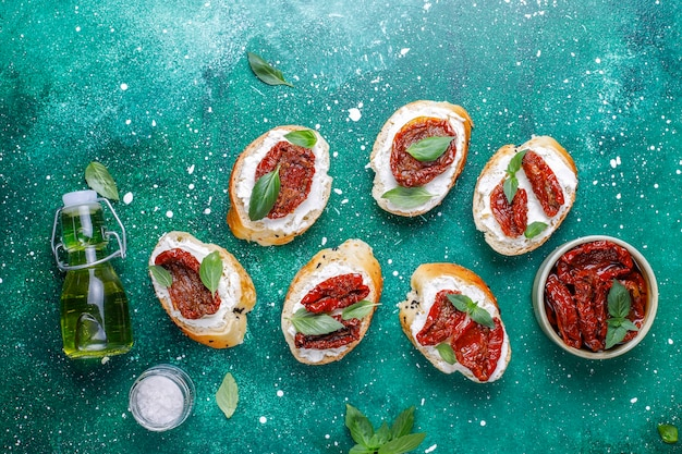Итальянские бутерброды - брускетта с сыром, сушеными помидорами и базиликом.