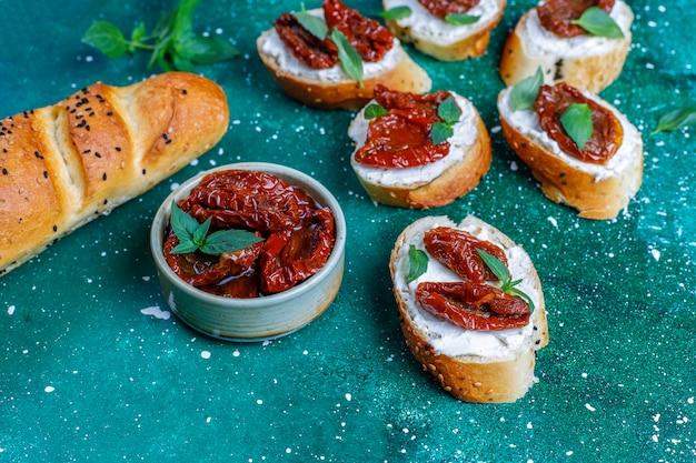 イタリアのサンドイッチ-チーズ、ドライトマト、バジルのブルスケッタ。