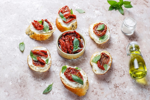 Italian sandwiches - bruschetta with cheese, dry tomatoes and basil
