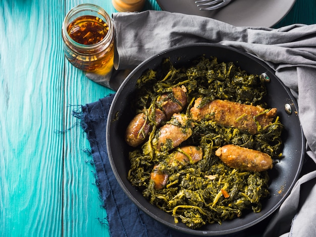 Italian sausages with rapini broccoli in a skillet