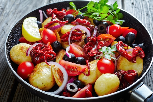 Italian seafood appetizer: baby octopus with new potatoes, olive oil, lemon juice, cherry tomatoes, red onion slices, black olives, parsley on a frying pan on a wooden table, close-up