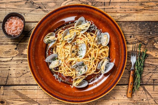 素朴なプレートにアサリを添えたイタリアンシーフードスパゲッティパスタ