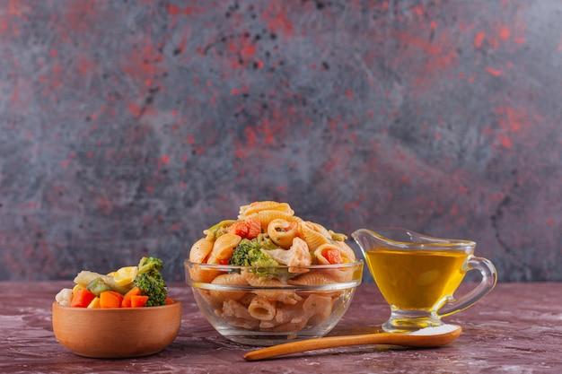 Итальянская паста с маслом и овощным салатом на светлом столе.