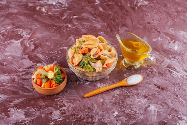 ライトテーブルに油と野菜のミックスサラダを添えたイタリアンシェルパスタ。
