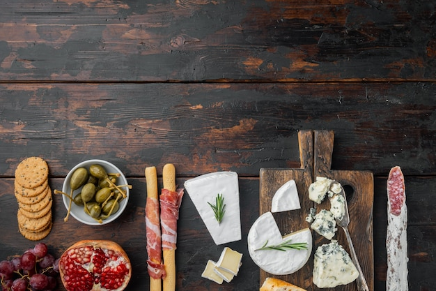 Italian snacks, meat cheese, herbs set, on dark wooden background, flat lay  with copy space for text