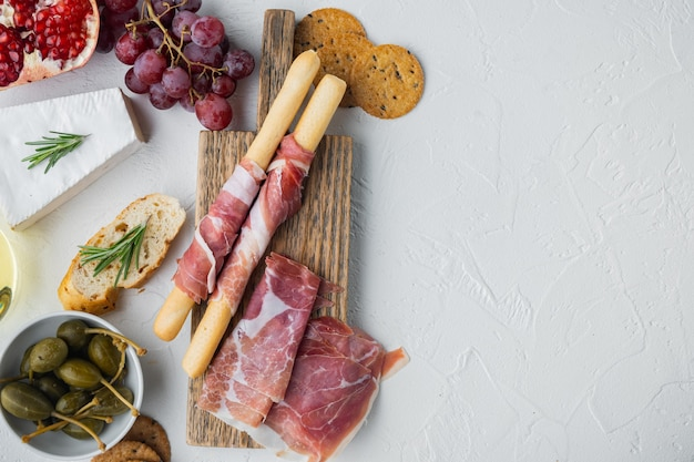 Italian snacks, meat cheese, herbs set, on white background, flat lay  with copy space for text