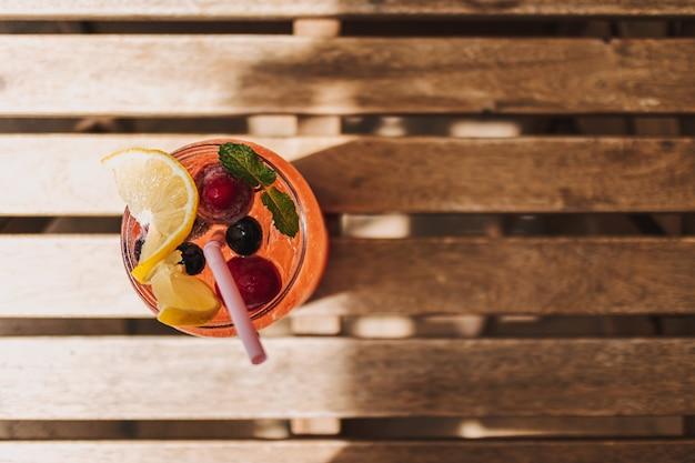 イタリアのソーダミックスベリーとレモンは夏に木製の机で提供されます