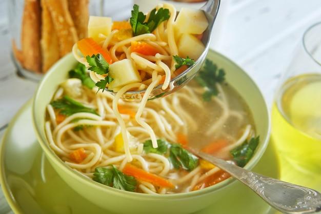 Итальянский суп со спагетти, морковью, лимоном, петрушкой и кусочками курицы в зеленой тарелке, на столе с салфетками, ложками хлеба и напитком в стакане