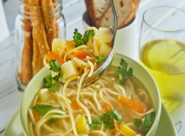 Italian soup with spaghetti, carrots, lemon, parsley and pieces of chicken in a green plate, on a table with napkins, spoons of bread and a drink in a glass