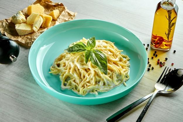 Итальянская паста спагетти с 4 видами сыра в сырном соусе, подается в голубой тарелке на деревянном столе. ресторанная еда. Premium Фотографии