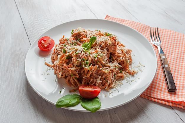 Итальянская паста спагетти с соусом и курицей, сыр пармезан и базилик. поверхность еды, плоская
