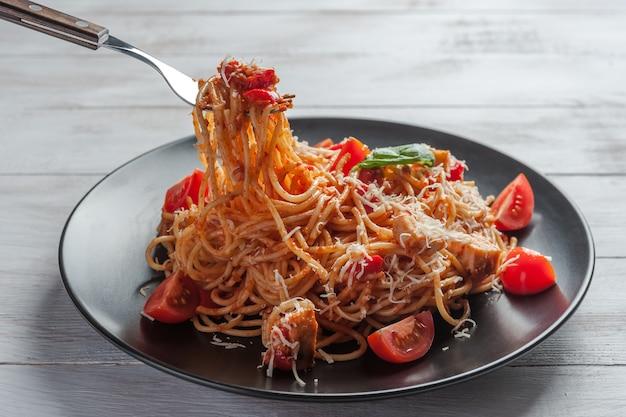 Итальянская паста спагетти с соусом и курицей, сыром пармезан и базиликом. пищевая стенка, плоская планировка