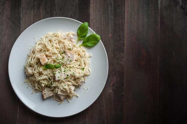 Итальянская паста спагетти с соусом и курицей, сыром пармезан и базиликом, y