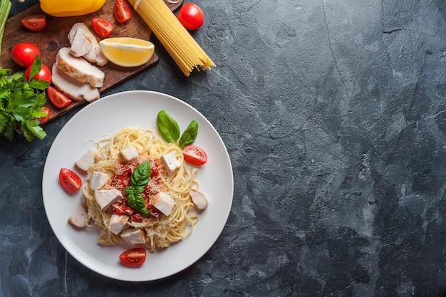 Итальянская паста спагетти с соусом и курицей, сыр пармезан и базилик.