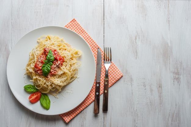 Итальянская паста спагетти с томатным соусом, сыром пармезан и базиликом.