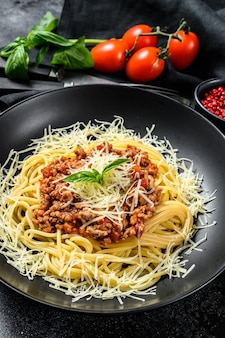 Italian spaghetti pasta with tomato sauce, cheese parmesan and basil