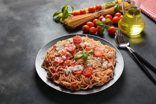 イタリアのスパゲッティパスタ、トマトソース、モッツァレラチーズ、チェリートマト、バジル