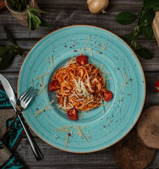 Italian spaghetti in tomato sauce with parmesan inside blue plate, top view.