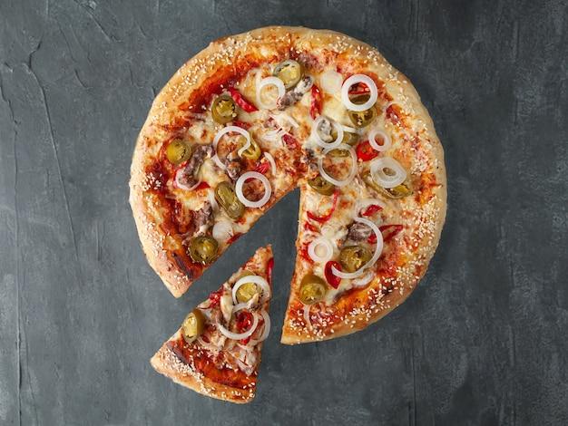 이탈리안 스파이시 피자. 다진 쇠고기, 양파, 핫 칠리 페퍼, 할라피뇨, 토마토 소스, 치즈와 함께. 피자에서 한 조각이 잘립니다. 위에서 볼. 회색 콘크리트 배경에. 외딴.
