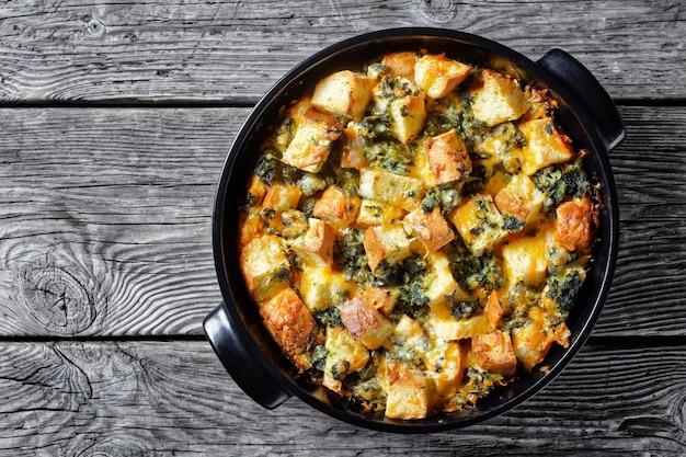 Слои итальянского шпината или запеканка для завтрака из нарезанного хлеба, запеченного с измельченным шпинатом и тертым сыром с горчицей, подается на черной форме для выпечки на деревянном фоне, вид сверху, копировальное пространство