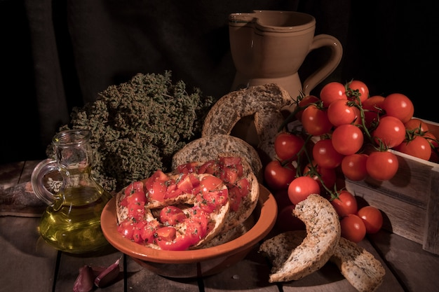 Italian starter friselle. classical frisella with tomato, salt, oregano and olive oil. dried bread called freselle. tipical apulian still-life of healthy vegetarian food
