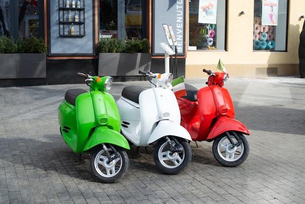 Итальянский стиль. ретро-скутеры в цветах флага италии у входа в ресторан. экспозиция и традиции