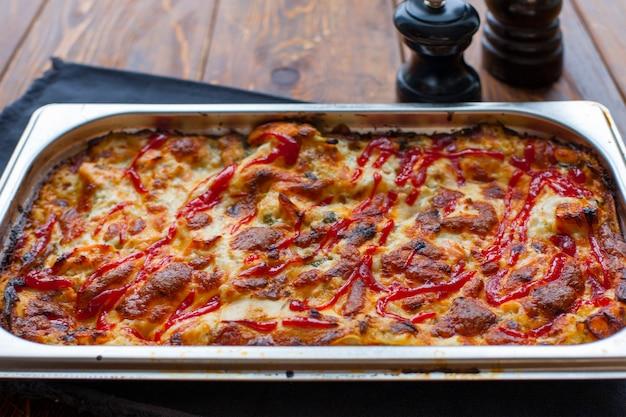 Итальянская вкусная лазанья в керамической запеканке на деревянном столе.