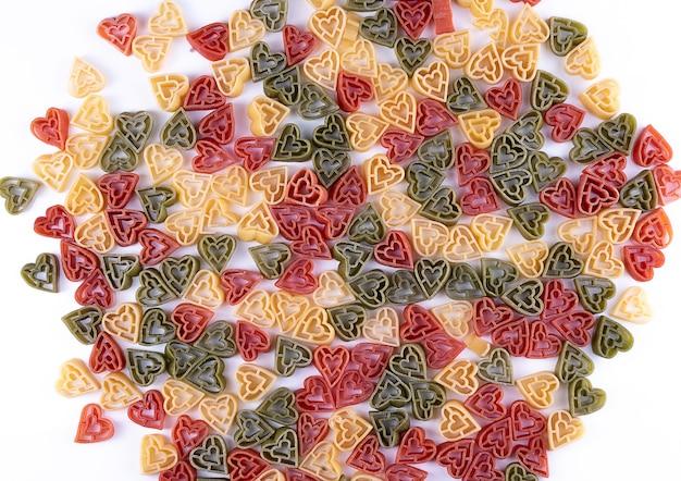 Итальянская трехцветная паста в форме сердца на белом