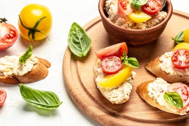 Итальянская брускетта из помидоров и сыра. тапас, закуски с нарезанными овощами, зеленью и маслом на багетном хлебе на гриле.