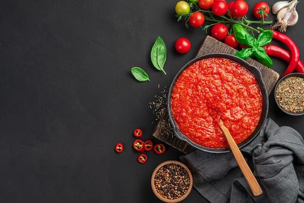 이탈리아 토마토 소스, 파스타 드레싱, 검은 배경에 프라이팬에 피자. 복사 공간