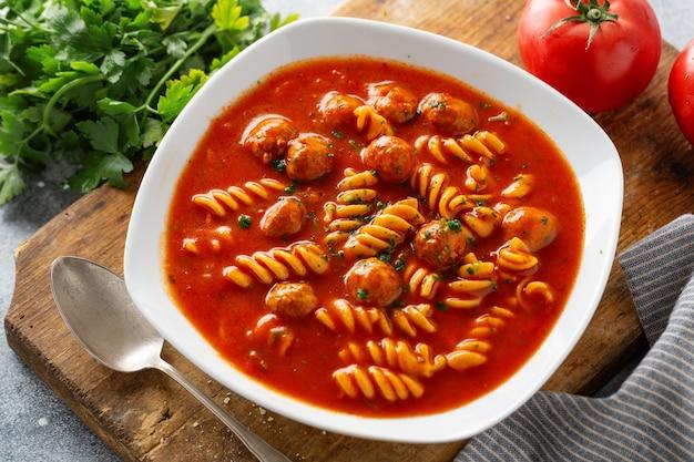 Итальянский томатный суп с лапшой и фрикадельками подается на тарелке.