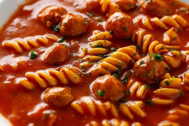Zuppa di pomodoro italiana con pasta e polpette di carne servite sul piatto.