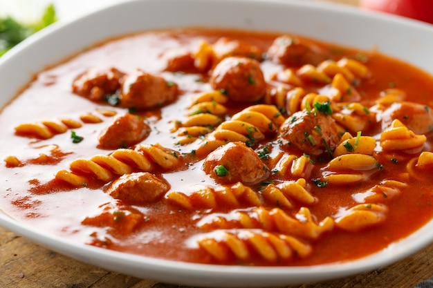 Italian tomato soup with noodles pasta and meatballs served on plate.