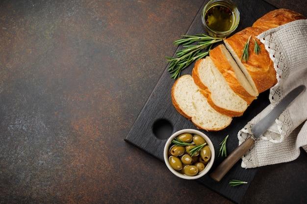 暗い石またはコンクリートの背景にオリーブ、オリーブオイル、コショウ、ローズマリーとイタリアの伝統的なチャバタパン。セレクティブフォーカス。上面図。スペースをコピーします。