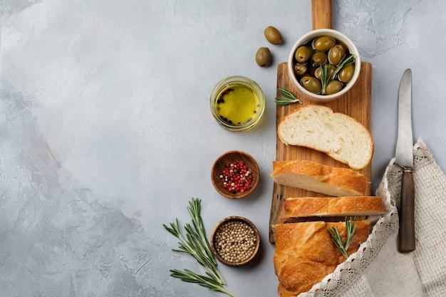 ライトグレーの石またはコンクリートの背景にオリーブ、オリーブオイル、コショウ、ローズマリーとイタリアの伝統的なチャバタパン。セレクティブフォーカス。上面図。スペースをコピーします。