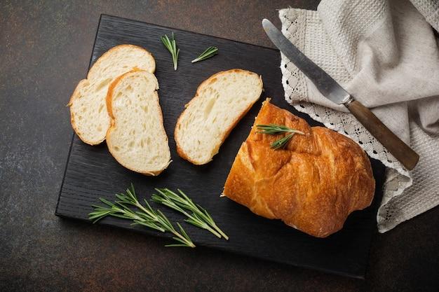 暗い石またはコンクリートの背景にローズマリーとイタリアの伝統的なチャバタのパン。セレクティブフォーカス。上面図。