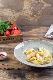 Italian traditional dish. pasta with salmon served on white plate, in the interior of the restaurant on a wooden table, tomatoes in the background and cutlery.