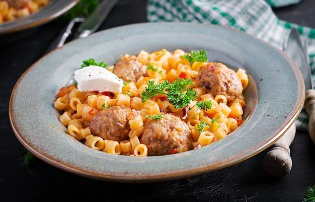 イタリアの伝統的なディタリーニパスタ。ミートボールのトマトソースと野菜のボウル。ディタリーニパスタとビーフボールのマリナーラトマトソース添え。