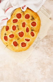 Итальянская традиционная выпечка хлеба фокачча с помидорами черри, пармезаном и розмарином на деревенской светло-коричневой стене. вид сверху.