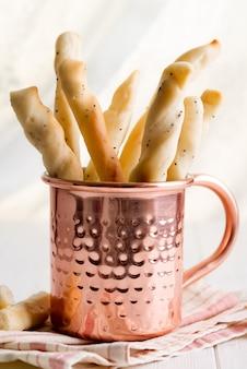 木製のテーブルの上に銅カップでイタリアの伝統的な自家製パン棒
