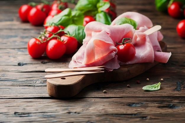 Italian traditional prosciutto with tomato and basil on the wooden table