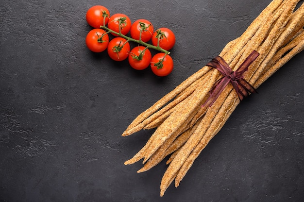 Italian traditional rye bread grissini and tomatoes cherry on on dark background.