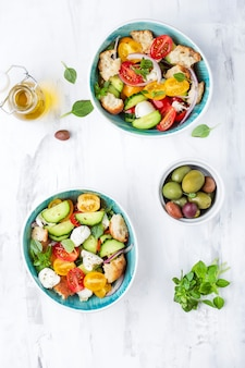 Italian traditional salad panzanella with fresh tomatoes and bread on a light background