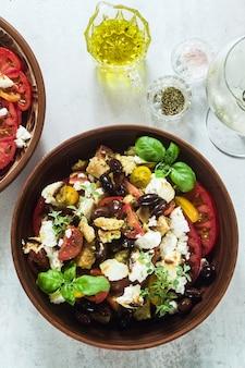 Итальянский традиционный тосканский салат панзанелла со свежими помидорами и сыром в глиняных тарелках и белым вином в бутылке и бокалах.